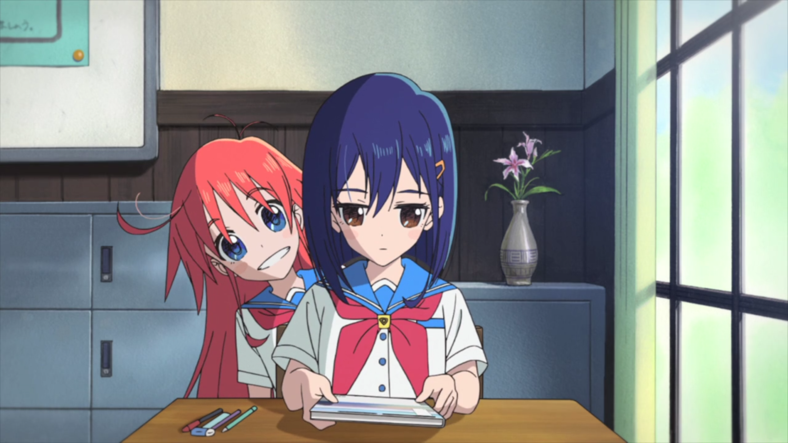 Cocona, a serious girl with blue hair and brown eyes sits at her school desk looking down at her book while Papika, a girl with red hair and blue eyes, smiles brightly from behind her.