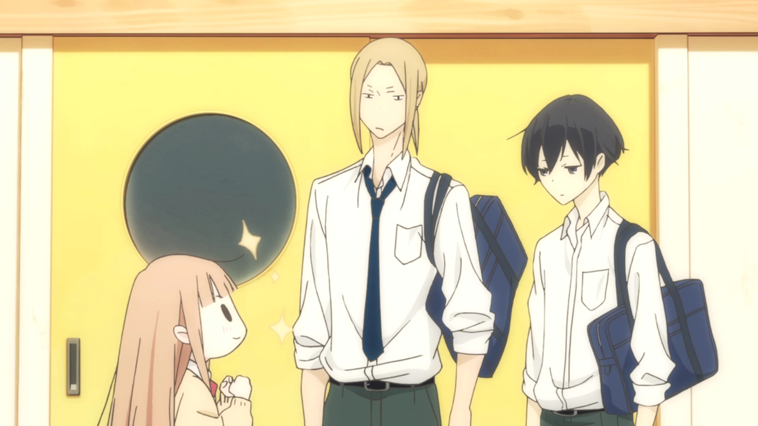 Short girl Miyano looks up at Ota and Tanaka with a determined smile on her face. Ota is tall with longer, sandy coloured hair, while Tanaka is average height with black hair and sleepy eyes.