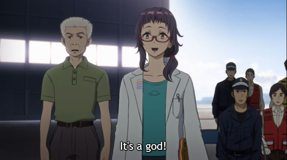 """A young female scientist with glasses and a ponytail smiles as an older male scientist and military officers stand behind her looking worried. Subtitle: """"It's a god!"""""""
