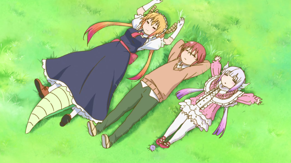 A woman in a casual sweater and pants (Kobayashi) lies on grass with her arms behind her head. On one side of her stretches out child dragon Kanna in human form wearing a frilly pink dress, while on the other side is Tohru, with her big dragon tail sticking out from underneath the petticoats of her Victorian maid costume.