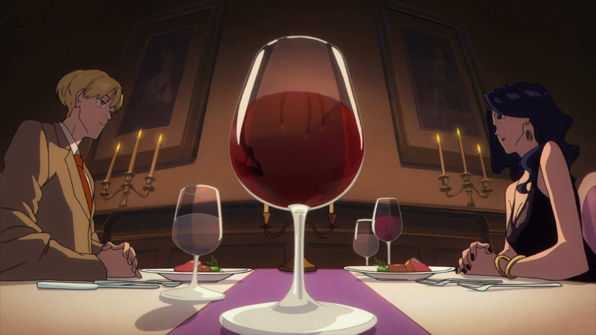 A fish-eye view of Mauve and Jean in formal clothing sat opposite each other over a diner table, with a large glass of red wine between the two, close to the camera.