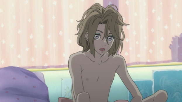 Kuranosuke, an attractive young man with feminine features, sits mostly undressed with bed hair., as comfortable as a half-naked boy as he is dressing and presenting as a girl.