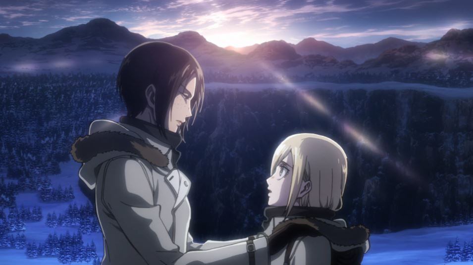 A tall dark-haired girl puts her hands on the shoulders of a short blonde girl as the sun rises over a mountain behind them