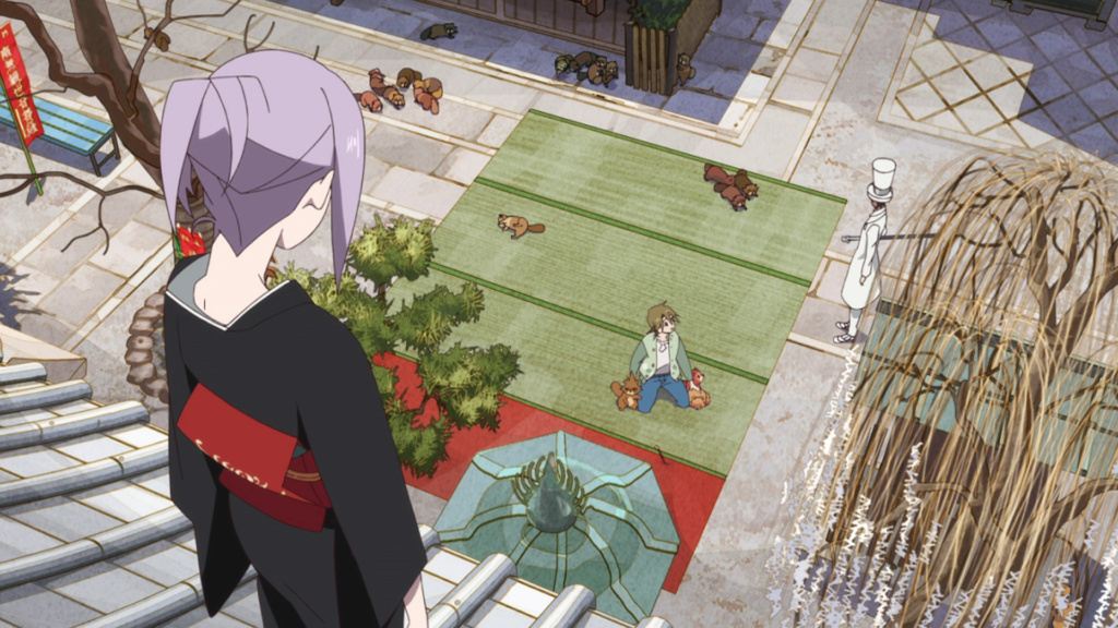 A woman in a kimono looks down on a temple square where a young man kneels, a man in a white top hat stands to the side, and several tanuki cower in fear