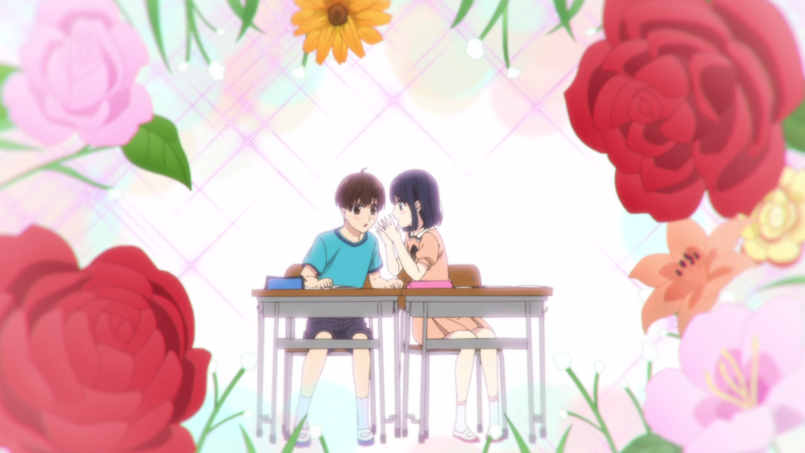 A girl and boy sit next to each other at school desks, the girl leaning over to whisper something to the boy, the whole frame surrounded by typical shojo flowers.