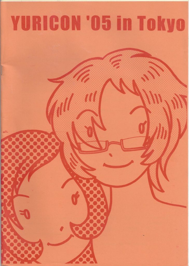 "A short-haired woman in glasses with another short-haired woman leaning on her shoulder. Text: ""Yuricon '05 in Tokyo"""