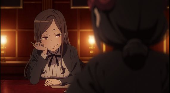 A long-haired girl in a school uniform sits at a table and smiles coyly at someone we can only see in profile from behind