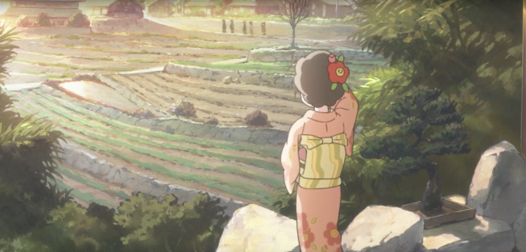 A woman in kimono with a flower in her hair faces away from the camera, looking out over a field bathed in sunset. There are people in the distance.