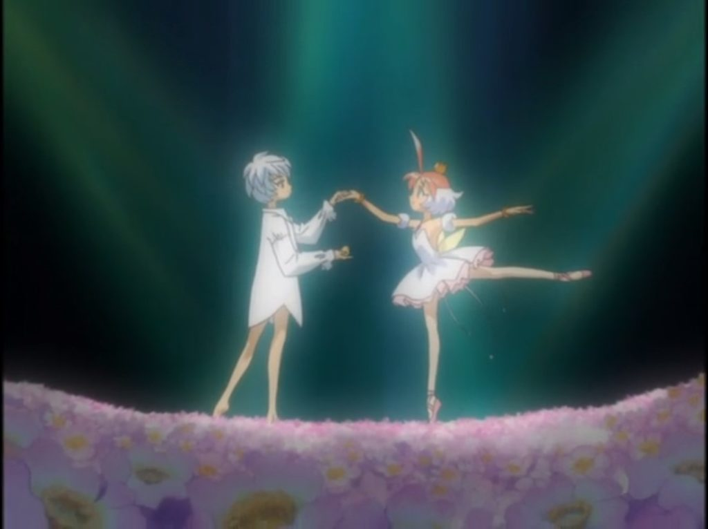 a white-haired boy wearing only a long shirt holds the hand of a ballerina standing en pointe.