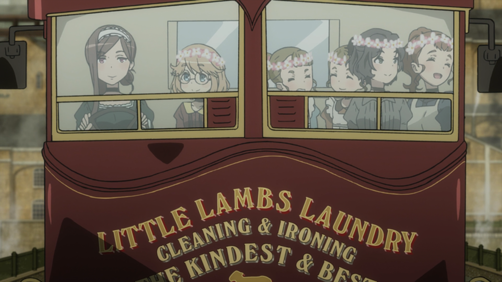 "A front view of women in a ""Little Lambs Laundry"" truck; a brunette is driving while the others smile beside her, wearing flower crowns"