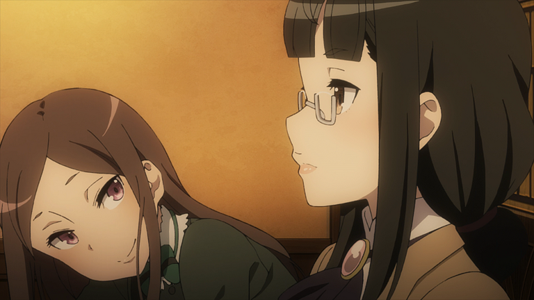 A young woman in glasses with neat dark hair sits in profile close to the camera; behind and to the left of her, another young woman with long brown hair leans forward, head tilted to the side, smiling slightly as she watches the woman in glasses