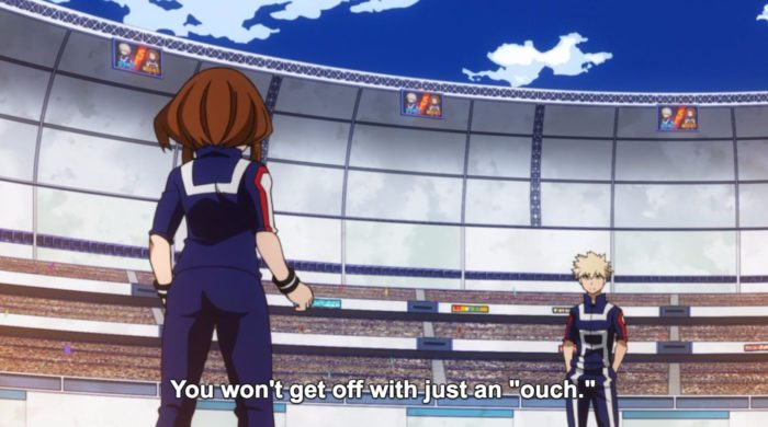 "Two people in blue track suits face each other in an arena. The brunette girl has her back to us; the white-haired boy faces us. Subtitles: ""You won't get off with just an 'ouch'."""