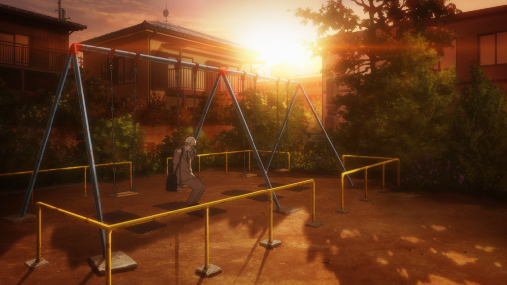A park at sunset. An older man sits on a swing set by himself, his head bent slightly.
