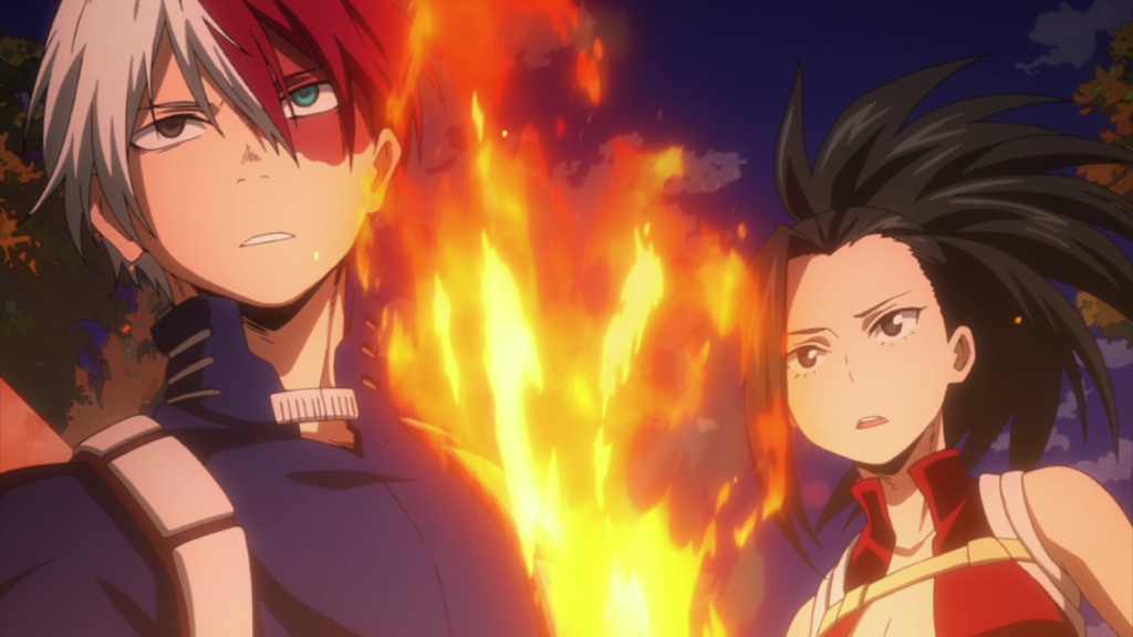 A boy with half-white, half-red hair and a burn scar across his left eye looks seriously into the distance. Behind him, a girl with her dark hair in ponytail wearing a red shirt cut down the middle looks concerned. There is a burst of fire between them.