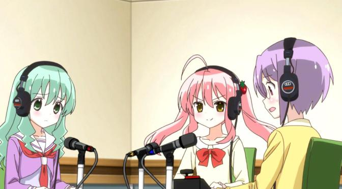 Three young women sit at a table wearing headphones. There are microphones in front of them. The one on the right is short-haired wearing glasses and looking nervous, the one in the middle has long pigtails and looks confident, and the one on the left has long hair falling over her shoulders and looks calm.