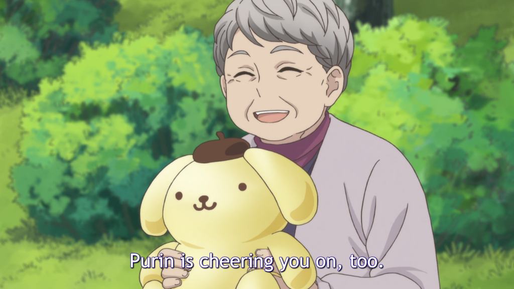 "An elderly woman with short hair wearing a cardigan smiles and holds up a plush smiling dog wearing a beret. Subtitles: ""Purin is cheering you on, too."""