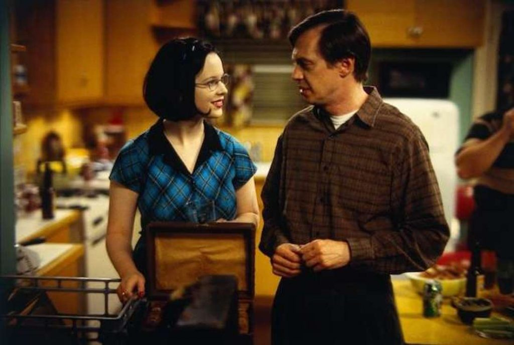 A live-action image of a teen girl in glasses standing in a kitchen with an older man; the two are smiling at each other.