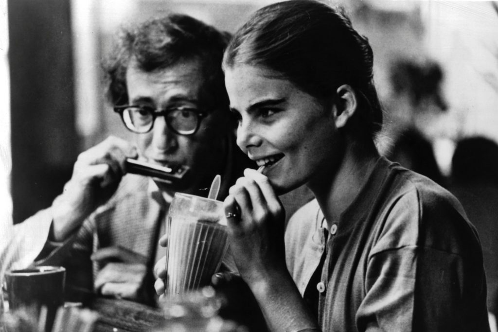 A black-and-white image of live-action teen girl drinking a milkshake while an older glasses-wearing man sets a harmonica to his lips behind her.