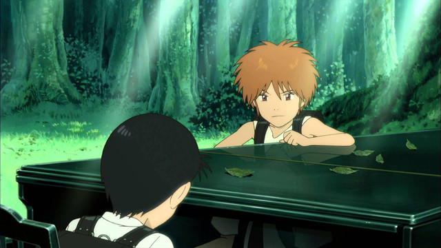A brunette kid with unkempt hair leans on a piano in the woods, looking suspicious, watching a black haired child play the instrument.