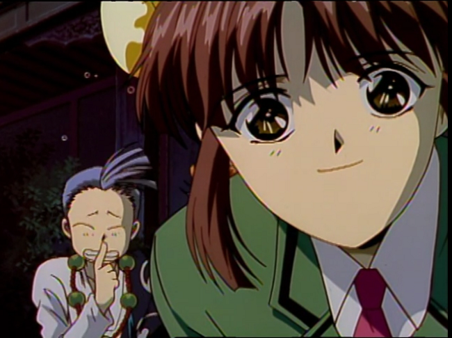 "A close-up of a teen girl in a school uniform smiling at the camera. To her right and behind her some distance, a monk with flyaway bangs wearing a robe and prayer beads presses a finger frantically to his lips as if to say ""shhh"""