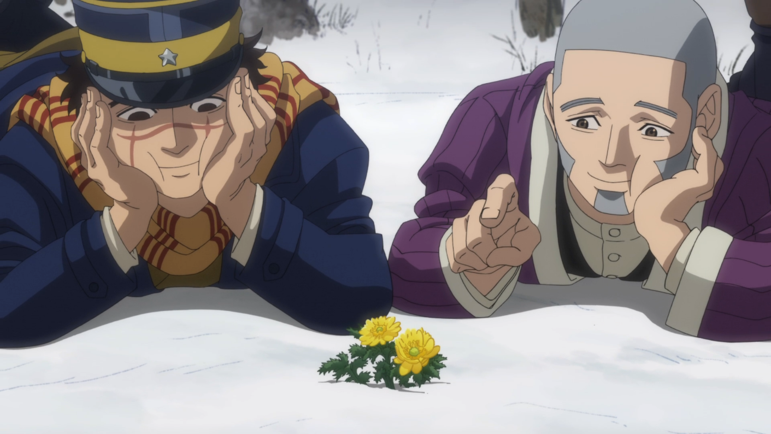 Two men, Sugimoto and Shiraishi, lay on their stomachs in the snow, admiring a tiny blooming yellow flower. Their cheeks are squished cutely between their hands and they're smiling.