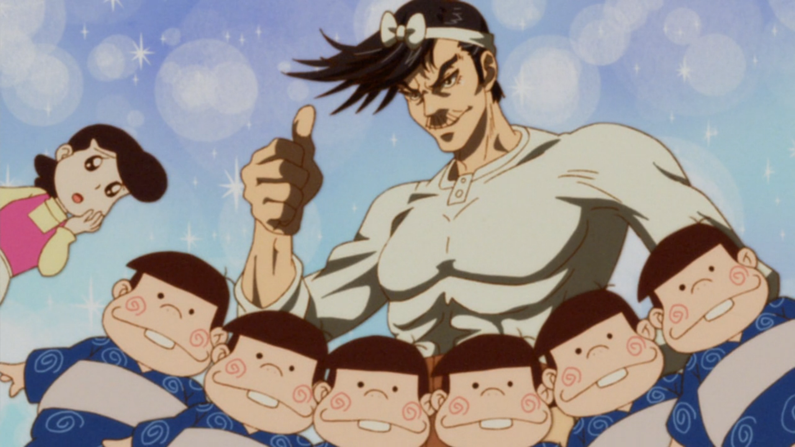 A buff older man stands behind a set of sextuplets and flashes a thumbs up. In the corner, a woman looks concerned.