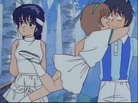 The three leads of Kimagure Orange Road dressed in tennis outfits. One girl throws her arms around the boy while the other girl looks away