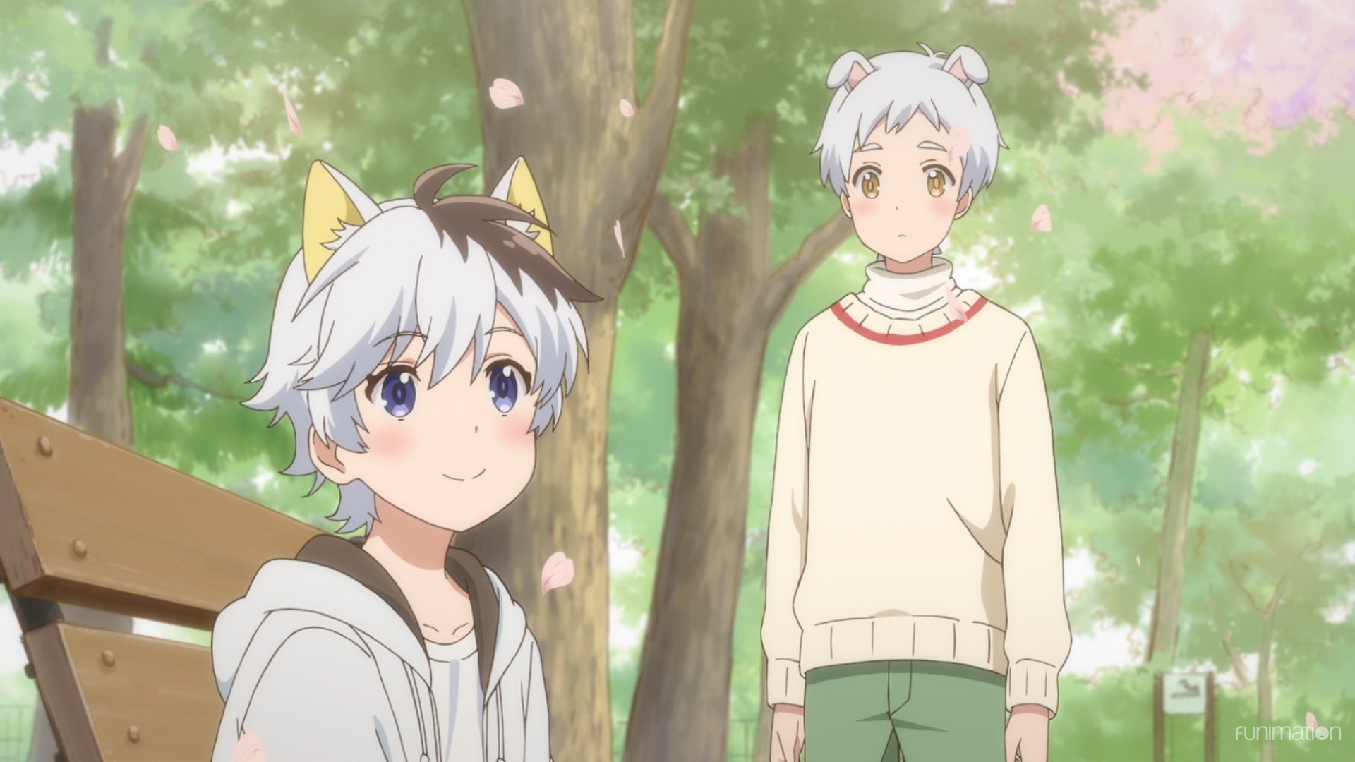 Two boys, one with dog ears and one with cat years sit in a park smiling